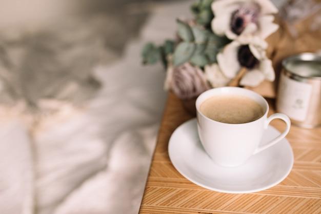 Manhã romântica. mesa de centro de madeira com flores na cama com manta, xícara de café, flores e velas. rosas lilases com eucalipto e anêmonas. tons de cinza interiores.