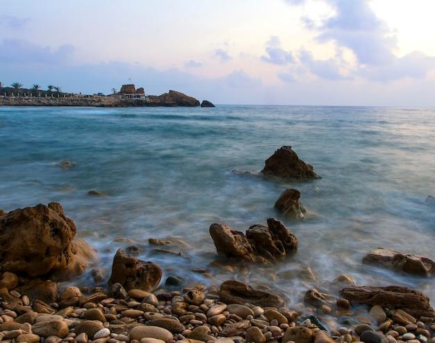 Manhã romântica no mar. grandes pedregulhos projetando-se do mar ondulado e liso.