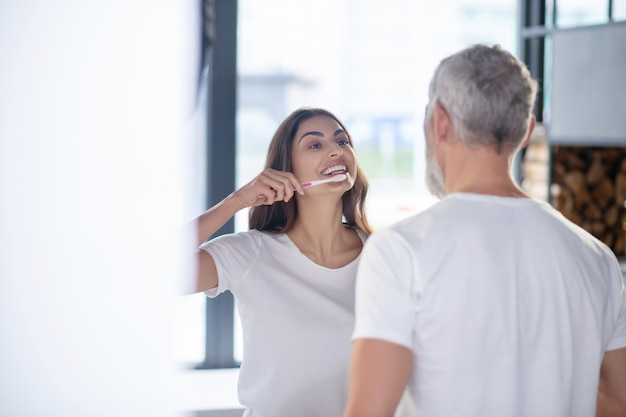 Manhã. uma mulher alegre escovando os dentes com o marido