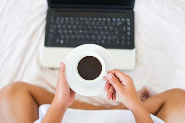 Manhã, xícara café, vista superior, mulher segura, xícara café, com, laptop, cama, em, a, manhã
