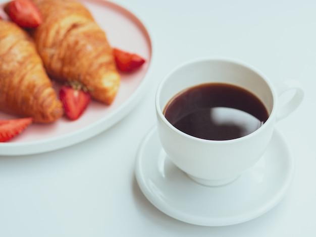 Manhã xícara de café e café da manhã prato com croissants e morangos