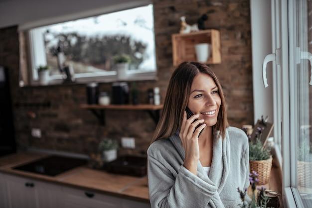 Manhãs de fim de semana. morena bonita que olha através da janela e que fala no telefone esperto no dia de inverno na cozinha acolhedor.