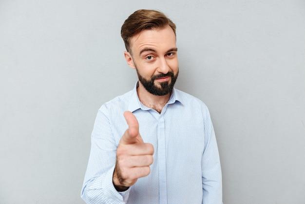 Manhoso sorridente barbudo homem com roupas de negócios, apontando para a câmera