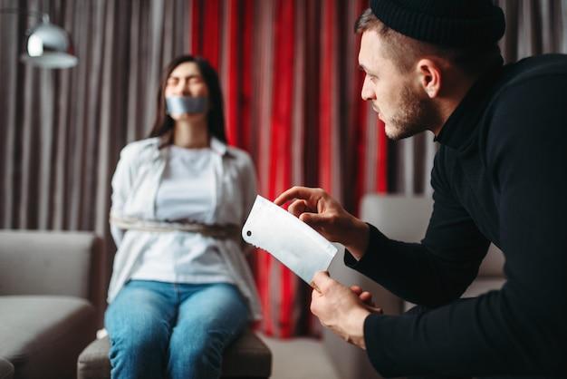 Maníaco ladrão em roupas pretas mostra uma faca afiada em sua vítima feminina, amarrada com corda e fita adesiva na cadeira. roubo em casa, gangster penetrou no apartamento