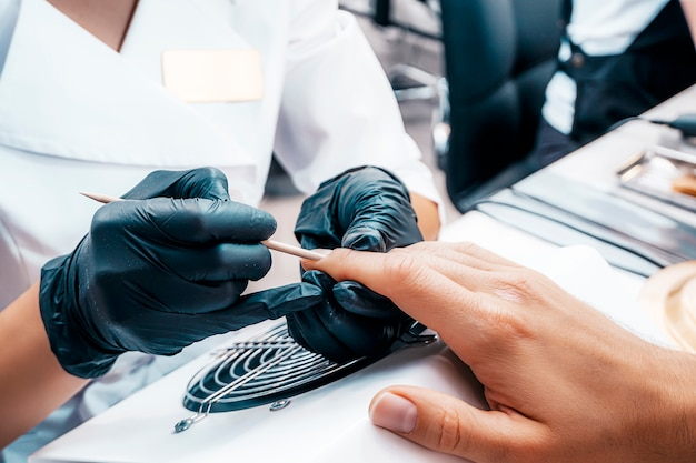 Manicura manicure um homem em um close-up do estúdio de beleza. close-up de mãos masculino bem preparado.