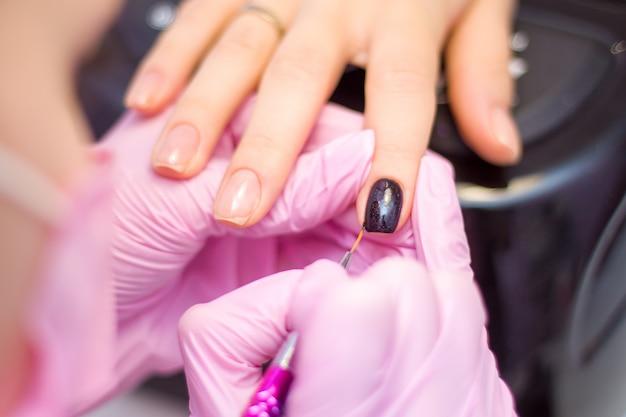 Manicure. as mãos do manicuro do close up em luvas cor-de-rosa estão pintando o verniz para as unhas preto nas unhas do cliente.