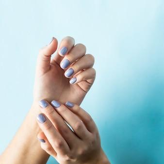 Manicure azul nas unhas femininas em um fundo azul