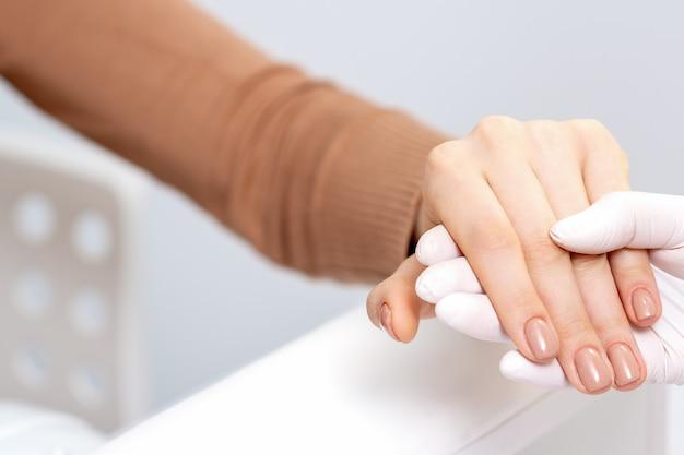 Manicure bege de mulher.