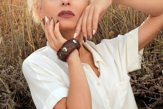 Manicure bege leitosa em uma garota loira com longas unhas ovais em um fundo de grama no verão