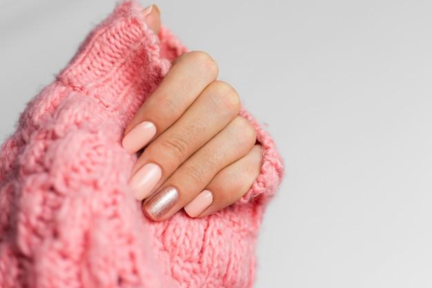 Manicure bonita cor nude, um dedo dourado brilhante, sobre fundo de malha de lã rosa