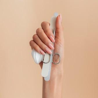 Manicure bonita e saudável segurando acessórios