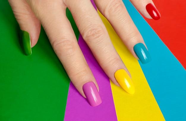 Manicure brilhante multicolorida com diferentes formas de unhas quadradas, ovais e afiadas em um fundo colorido.
