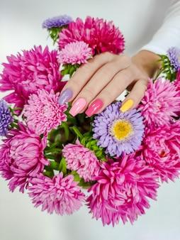 Manicure colorida em unhas compridas com um buquê de ásteres