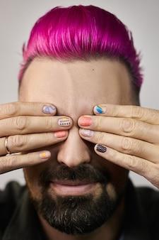 Manicure com design criativo nos dedos de um homem, cabelo roxo na cabeça de um cara. cuidados com as unhas das mãos