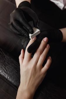 Manicure com luvas pretas, unidade de polimento, polidor que trata as unhas. prepara para extensão da unha. instalações de spa. sala de manicure.