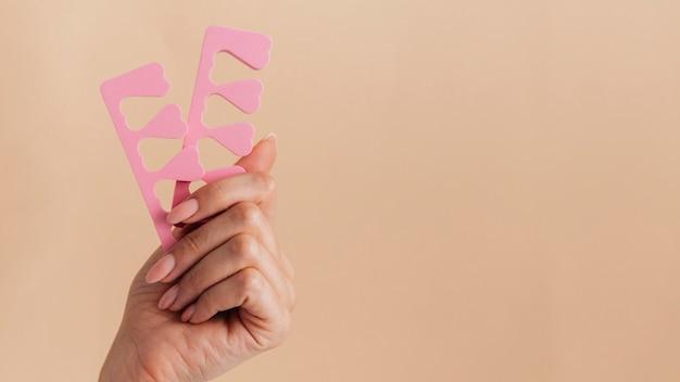 Manicure cuidados saudáveis segurando acessórios de unha rosa
