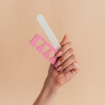 Manicure cuidados saudáveis segurando acessórios para unhas