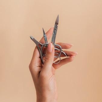 Manicure cuidados saudáveis segurando uma tesoura