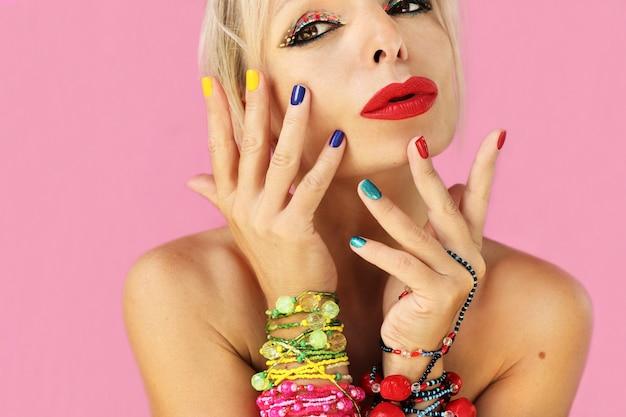Manicure curta multicolorida e maquiagem em uma garota com joias de miçangas