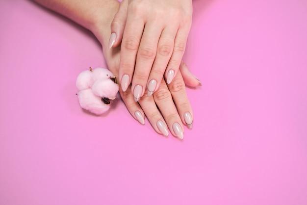 Manicure de mulher bonita em tons delicados, sobre um fundo brilhante com algodão rosa suave.