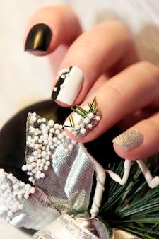 Manicure de natal preto e branco com bolas de prata e enfeite de natal na mão feminina close-up.