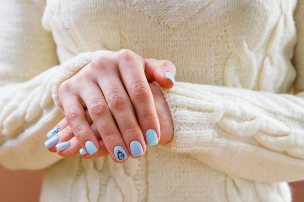 Manicure delicada em tons pastel para uma garota em um fundo de roupas