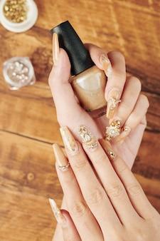 Manicure dourada com strass