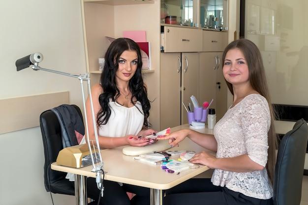 Manicure e cliente em salão de beleza com paleta de unhas