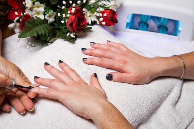 Manicure e mãos com lâmpada de uv para unhas