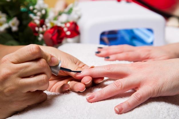 Manicure e mãos com lâmpada uv para unhas