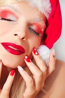 Manicure e maquiagem de ano novo com flocos de neve nos olhos e nas mãos.