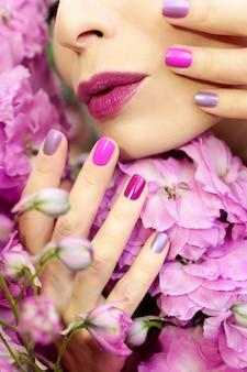 Manicure e maquiagem roxas fecham em uma garota com uma flor delphinium.