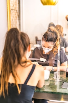 Manicure e pedicure com medidas de segurança, máscaras e telas de plástico. reabertura após a pandemia de corod-19. coronavírus