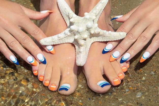 Manicure e pedicure francesa de azul marinho com uma estrela do mar no fundo de areia da praia