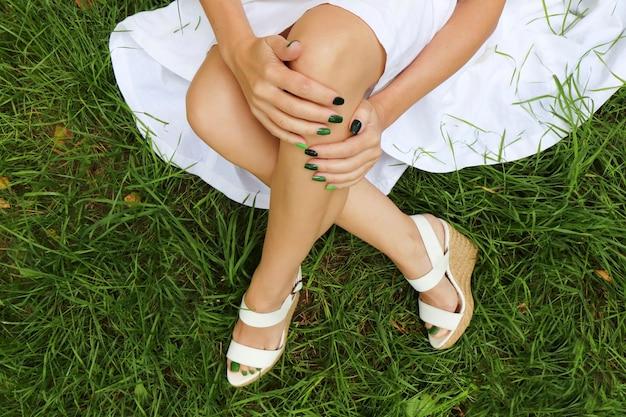 Manicure e pedicure verdes coloridas com saltos em cunha branca no fundo da grama
