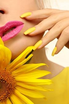 Manicure elegante em unhas compridas cobertas com esmalte amarelo.