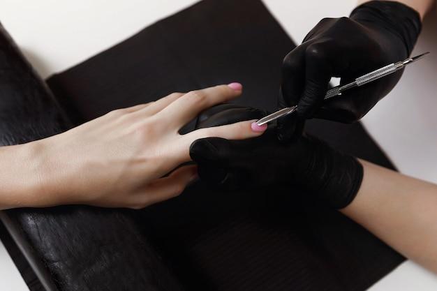 Manicure em luvas pretas, empurradora, prepara as unhas para procedimentos. extensão de unha. instalações de spa. sala de manicure.