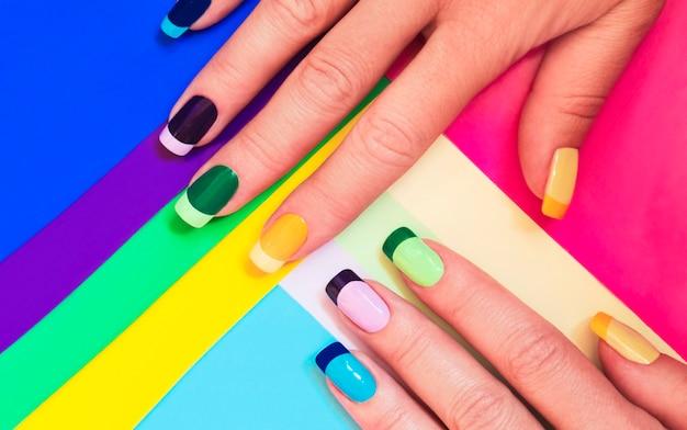 Manicure em tons pastel multicoloridos combinando tom sobre tom com uma superfície listrada.