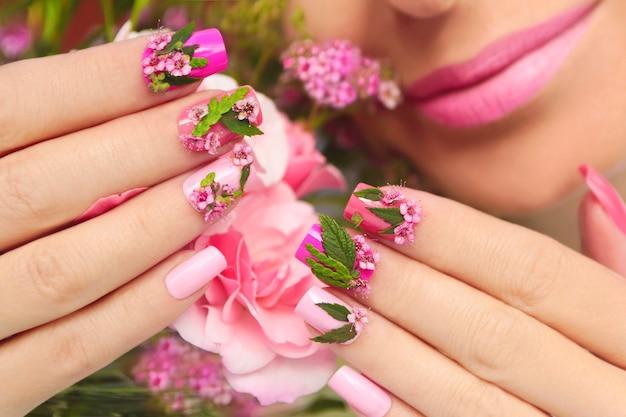 Manicure em tons pastel multicoloridos em mãos femininas