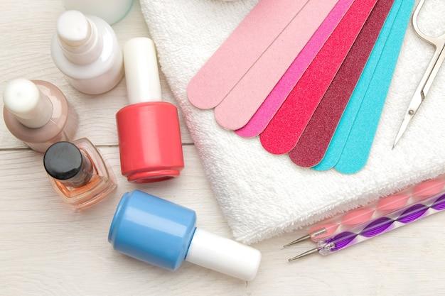 Manicure. esmaltes e vários acessórios e ferramentas para manicure em uma mesa de madeira branca. vista do topo