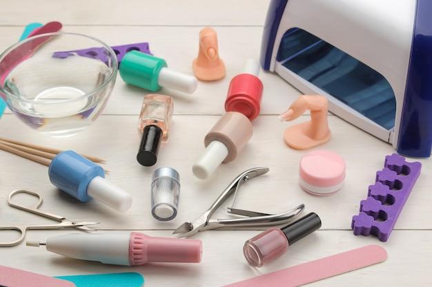 Manicure. esmaltes e vários acessórios e ferramentas para manicure em uma mesa de madeira branca