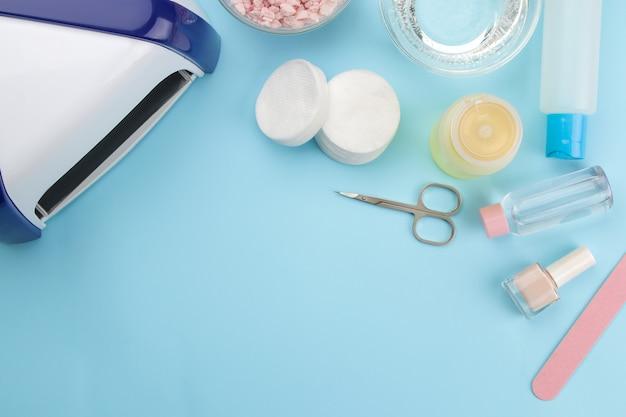 Manicure. esmaltes, lâmpada uv e vários acessórios e ferramentas para manicure em um fundo azul da moda. vista do topo