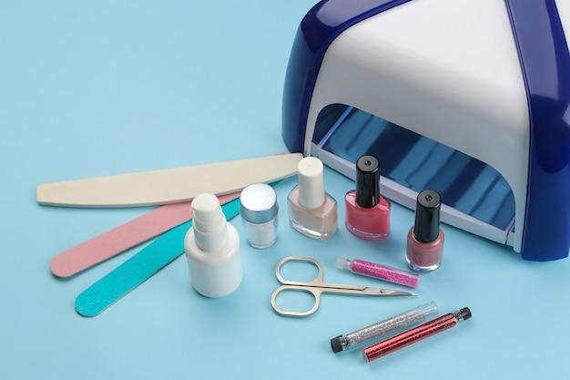 Manicure. esmaltes, lâmpada uv e vários acessórios e ferramentas para manicure em um fundo azul da moda.