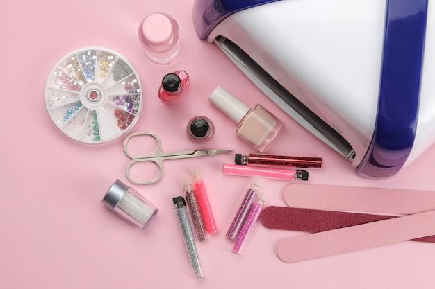 Manicure. esmaltes, lâmpada uv e vários acessórios e ferramentas para manicure em um fundo rosa na moda. vista do topo