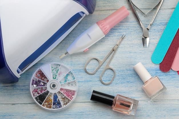 Manicure. esmaltes, lâmpada uv e vários acessórios e ferramentas para manicure em uma mesa de madeira azul. vista do topo