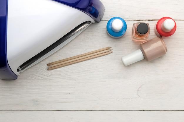Manicure. esmaltes, lâmpada uv e vários acessórios e ferramentas para manicure em uma mesa de madeira branca. vista do topo