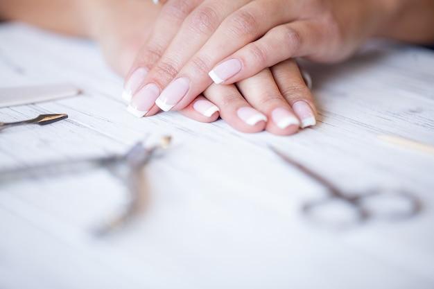 Manicure. fechar as mãos femininas, situando na mesa perto de ferramentas de unha