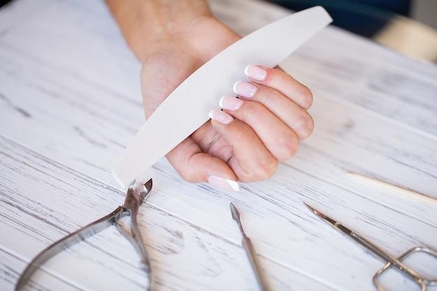 Manicure. feche acima das mãos fêmeas que situam na mesa perto das ferramentas do prego