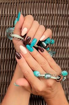 Manicure feminina com esmalte azul e marrom com decoração