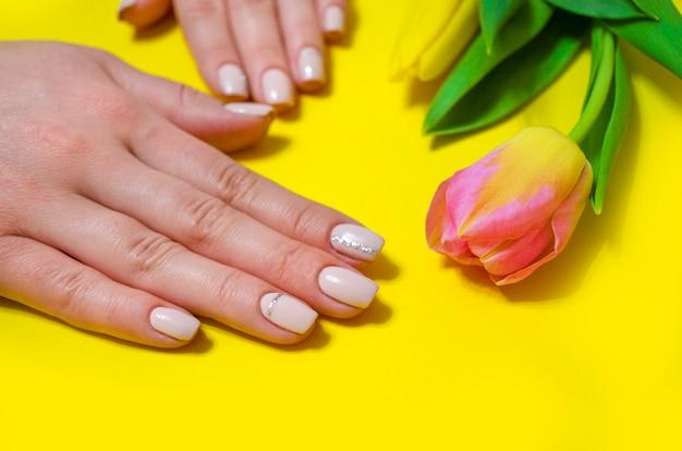 Manicure feminina em um fundo brilhante. fundo amarelo com tulipas. bandeira.